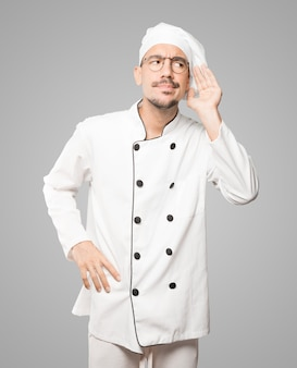 Geconcentreerde jonge chef-kok die een gebaar maakt om iets te proberen te horen