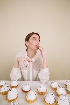 Geconcentreerde jonge dame poseren tijdens het eten van cupcakes.