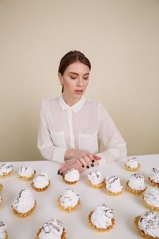 Geconcentreerde jonge dame poseren zittend in de buurt van cupcakes