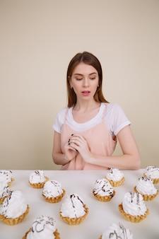 Geconcentreerde jonge dame zitten en poseren in de buurt van cupcakes