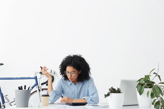 Geconcentreerde jonge donkere vrouwelijke accountant maakt verslag