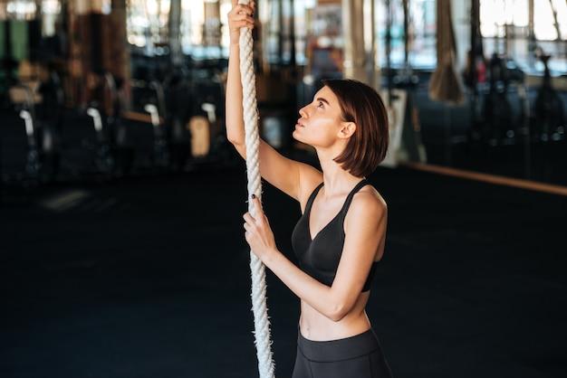 Geconcentreerde jonge fitness vrouw klimmen op het touw in de sportschool