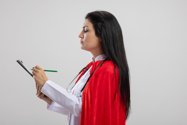 Geconcentreerde jonge kaukasische superheld meisje dragen stethoscoop staande in profiel te bekijken schrijven met potlood op klembord geïsoleerd op een witte achtergrond met kopie ruimte