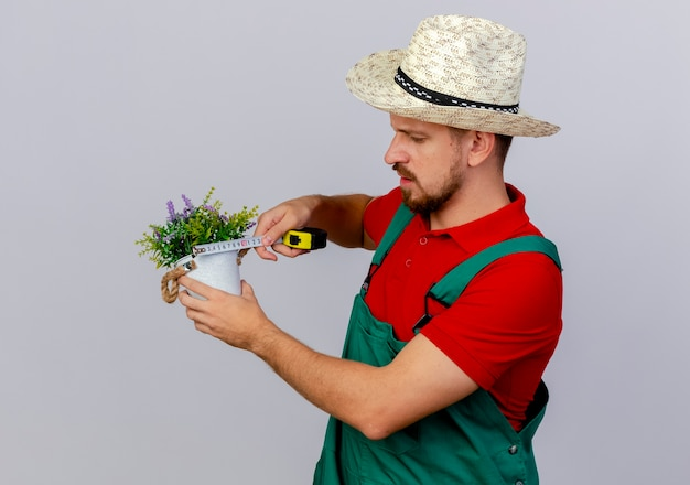 Geconcentreerde jonge knappe slavische tuinman in uniform en hoed met bloempot en meetlint meten geïsoleerd