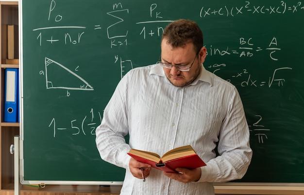 Geconcentreerde jonge leraar met een bril die voor het bord in de klas staat met de aanwijzerstok leesboek