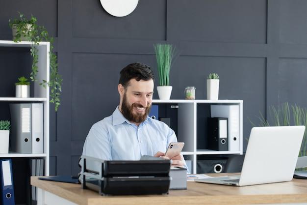 Geconcentreerde jonge man aan het werk op laptop thuis kantoor