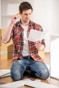 Geconcentreerde jonge man die de instructies leest.