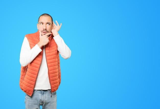 Geconcentreerde jonge man die een gebaar maakt om te proberen iets te horen