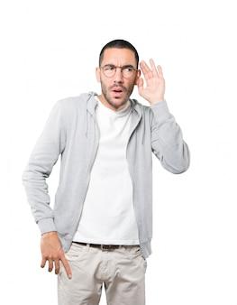 Geconcentreerde jonge man die een gebaar maakt van proberen iets te horen