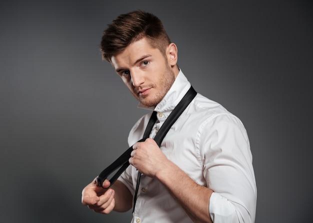 Geconcentreerde jonge man gekleed in formalwear