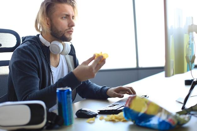 Geconcentreerde jonge man in casual kleding met behulp van computer, streaming playthrough of walkthrough video en chips eten.