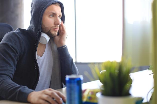 Geconcentreerde jonge man in casual kleding met behulp van computer, streaming playthrough of walkthrough video.