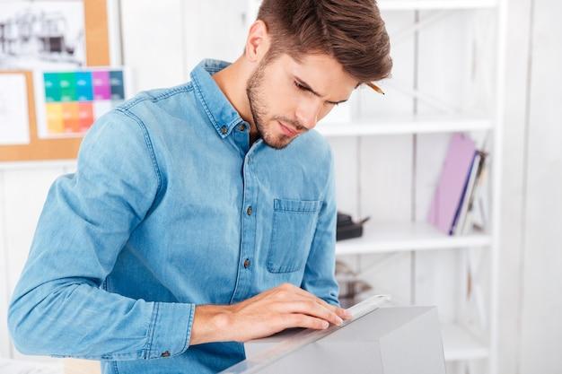 Geconcentreerde jonge man meetdoos met liniaal terwijl hij op kantoor zit