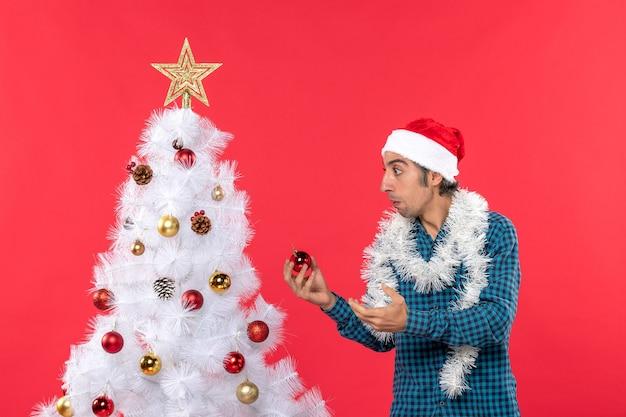 Geconcentreerde jonge man met kerstman hoed in een blauw gestreept overhemd en decotaion accessoire staande te houden