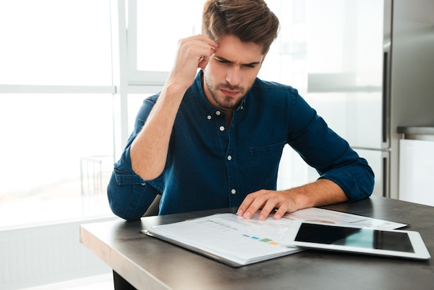 Geconcentreerde jonge man om thuis te zitten en zijn financiën te analyseren. documenten bekijken en zijn hoofd aanraken