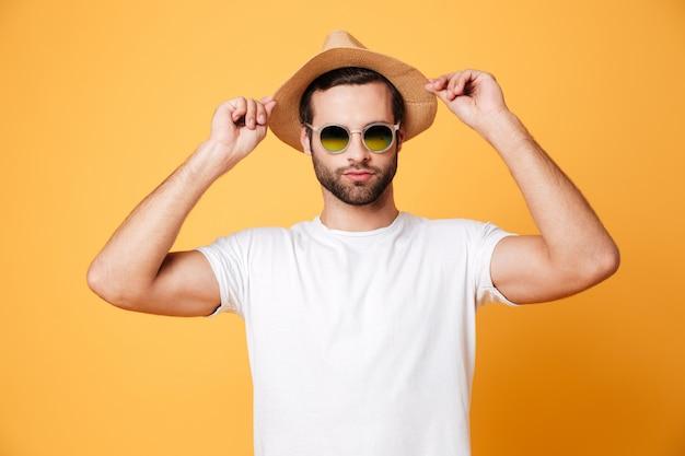Geconcentreerde jonge man staande geïsoleerd over oranje muur