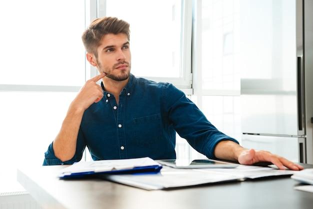 Geconcentreerde jonge man thuis na te denken over financiën. kijk opzij en raak zijn gezicht aan