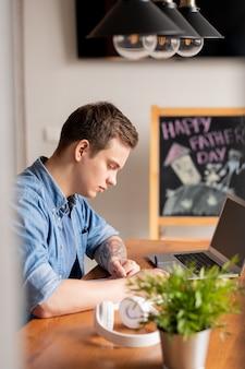 Geconcentreerde jonge mannelijke freelancer in denim overhemd aan tafel zitten met laptop en taken opschrijven