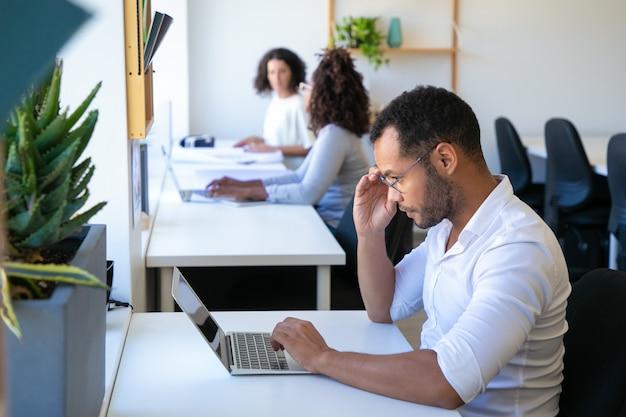 Geconcentreerde jonge mens die laptop bekijkt