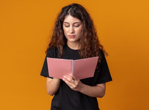 Geconcentreerde jonge mooie vrouw die met potlood op notitieblok schrijft dat op oranje muur met exemplaarruimte wordt geïsoleerd