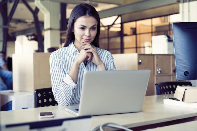 Geconcentreerde jonge mooie zakenvrouw die op laptop in heldere, moderne kantoren werkt