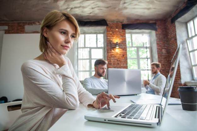 Geconcentreerde jonge mooie zakenvrouw die op laptop werkt in een helder modern kantoor.