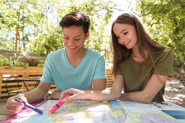 Geconcentreerde jonge multi-etnische vriendenstudenten in openlucht