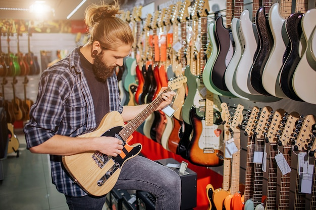 Geconcentreerde jonge muzikant staan en spelen op elektrische gitaar. hij kijkt ernaar. guy is in de muziekwinkel. jonge hipster concentreerde zich op spelen.