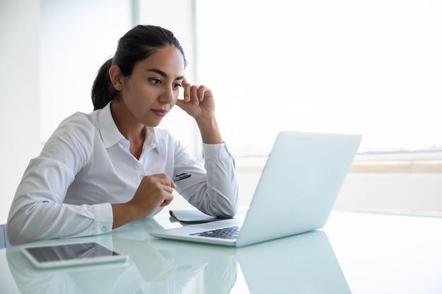Geconcentreerde jonge onderneemster die laptop in bureau met behulp van