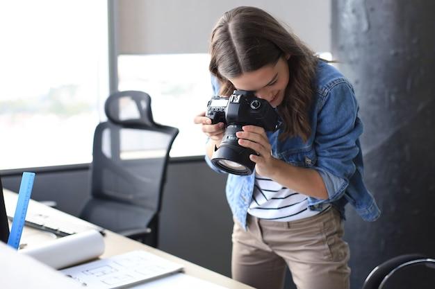 Geconcentreerde jonge ontwerper die digitale camera gebruikt terwijl ze bij het bureau in haar creatieve kantoor staat.