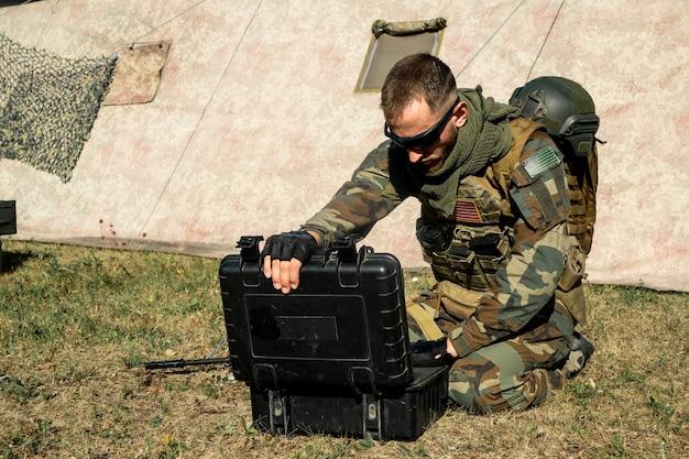 Geconcentreerde jonge programmeur-soldaat die op de grond zit en met een laptop werkt terwijl hij de legerroute analyseert