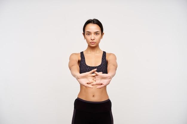 Geconcentreerde jonge sportieve vrouw met bruine ogen en casual kapsel dat haar vingers kruist terwijl ze handen uitrekt, ochtendtraining doet terwijl ze over een witte muur staat