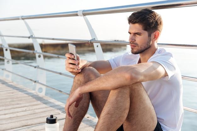 Geconcentreerde jonge sportman die op de pier zit en smartphone gebruikt