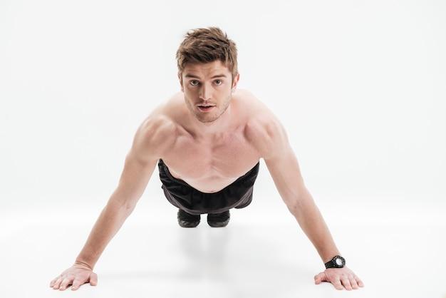 Geconcentreerde jonge sportman die opdrukoefeningen doet