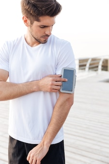 Geconcentreerde jonge sportman die smartphone in armband buitenshuis gebruikt