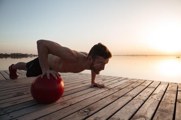 Geconcentreerde jonge sportman maakt sportoefeningen met bal