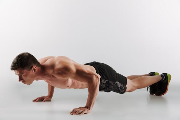 Geconcentreerde jonge sportman maakt sportoefeningen