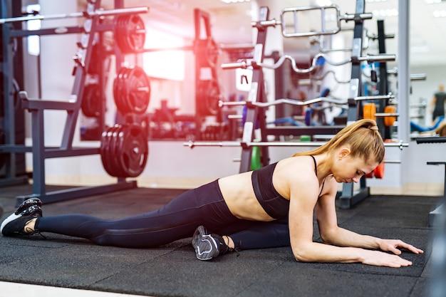 Geconcentreerde jonge sportvrouw trainingsvloer boven de fitnessclub. gespierd meisje doet haar gezonde training binnenshuis.