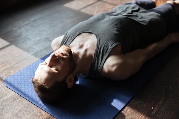 Geconcentreerde jonge sterke sportman in de sportschool ligt op de vloer