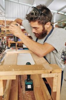Geconcentreerde jonge timmerman die schroeven in houten kruk drijft