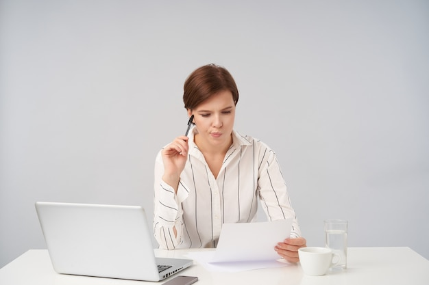Geconcentreerde jonge vrij kortharige brunette vrouw met pen in opgeheven hand en kijken naar stuk papier met bezorgd gezicht, worringly haar lippen bijten tijdens het opstellen van rapport
