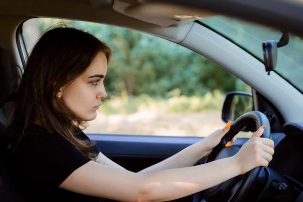 Geconcentreerde jonge vrouw bestuurder rijdt snelle auto en het beheersen van de situatie