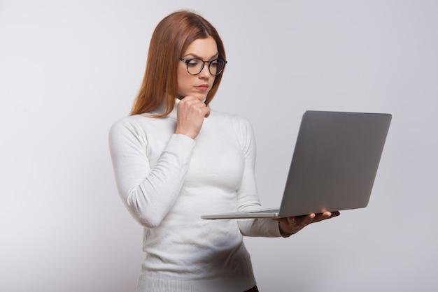 Geconcentreerde jonge vrouw die laptop met behulp van