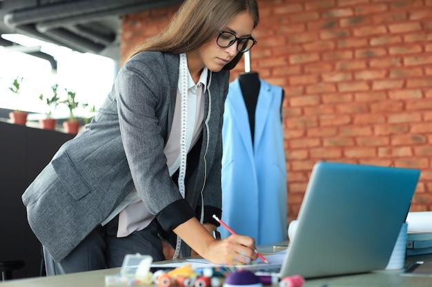 Geconcentreerde jonge vrouw die met laptop werkt terwijl ze in haar studio werkt.