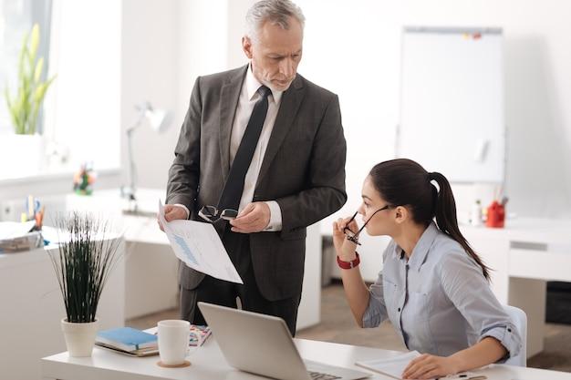 Geconcentreerde jonge vrouw die slimme horloges draagt en haar linkerhand op de tafel legt terwijl ze naar documenten kijkt