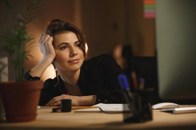 Geconcentreerde jonge vrouw ontwerper zitten in kantoor 's nachts