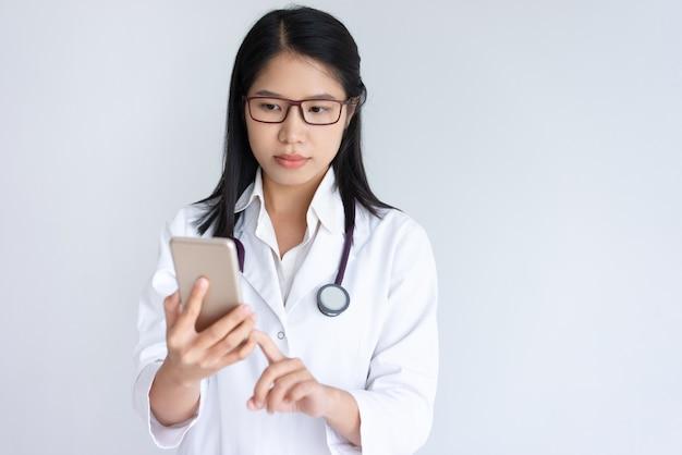 Geconcentreerde jonge vrouwelijke arts die smartphone gebruikt