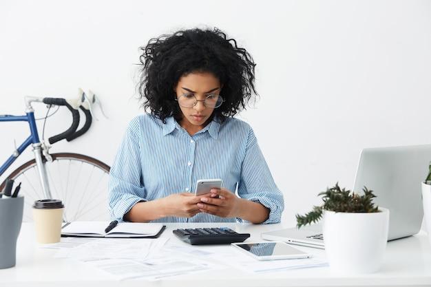 Geconcentreerde jonge vrouwelijke secretaris van gemengd ras die dringend bericht leest