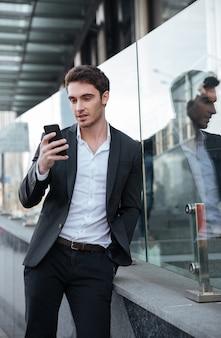 Geconcentreerde jonge zakenman die dichtbij commercieel centrum loopt