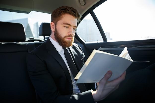 Geconcentreerde jonge zakenman die documenten analyseert tijdens het reizen